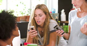 Amici femminili che producono prima colazione mentre controllando telefono cellulare archivi video