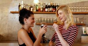Amici femminili che si abbracciano felicemente mentre avendo bevande alla barra 4K 4k video d archivio
