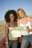 Amici femminili con la mappa che si appoggia automobile Immagini Stock Libere da Diritti