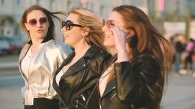 Amici femminili delle signore allegre che godono del tramonto urbano stock footage