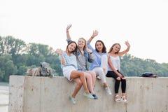 Amici femminili divertendosi sul fine settimana, sul picnic all'aperto Giovani sorridenti che si siedono sul confine concreto e c fotografia stock libera da diritti