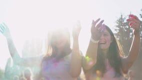 Amici femminili felici che gettano nella polvere variopinta dell'aria, fest di holi, rallentatore archivi video