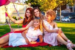 Amici femminili felici che giocano e che si divertono nell'erba verde immagini stock libere da diritti