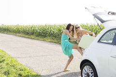 Amici femminili felici che spingono bagagli nel tronco di automobile contro il chiaro cielo Fotografia Stock Libera da Diritti