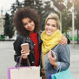 Amici femminili felici con i sacchetti della spesa all'aperto Immagine Stock Libera da Diritti