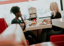 Amici femminili multirazziali che mangiano alimenti a rapida preparazione ad una tavola nei Di fotografia stock
