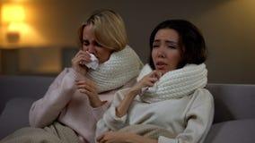 Amici femminili in sciarpe che starnutiscono nel tessuto, influenza di sofferenza, epidemia di inverno immagini stock