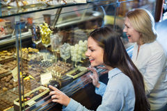 Amici femminili sorridenti allegri che selezionano il cioccolato fine ed il co Immagini Stock Libere da Diritti