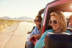Amici femminili sul viaggio stradale dietro all'automobile convertibile immagini stock