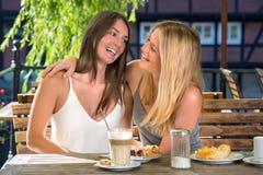 Amici femminili vicini in caffè della via Fotografia Stock
