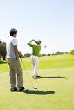 Amici Golfing che collocano sul tee fuori Immagini Stock
