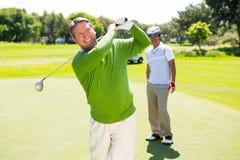 Amici Golfing che collocano sul tee fuori Fotografie Stock Libere da Diritti