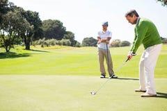 Amici Golfing che collocano sul tee fuori Fotografia Stock
