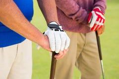 Amici Golfing che stanno e che tengono i club Immagini Stock