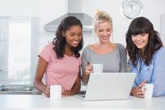 Amici graziosi che mangiano caffè insieme e che esaminano computer portatile Immagini Stock