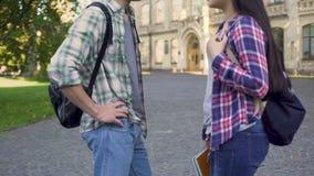 Amici il più bene femminili e maschii che chiacchierano vicino all'accademia, discutente prova passata stock footage