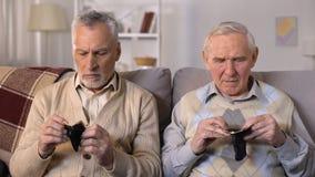Amici maschii anziani insoddisfatti che mostrano i portafogli vuoti alla macchina fotografica, povertà video d archivio