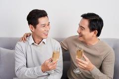 Amici maschii asiatici e sedersi sul sofà e sul champang bevente fotografia stock libera da diritti