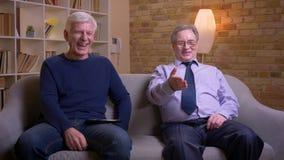Amici maschii caucasici anziani che guardano insieme film della commedia sulla TV che ride essendo allegro stock footage