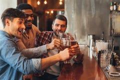Amici maschii che bevono birra e che parlano in Antivari fotografie stock libere da diritti