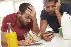 Amici maschii che controllano i telefoni dopo l'invio del testo mentre ubriaco fotografie stock