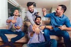 Amici maschii che giocano i video giochi a casa e divertiresi immagini stock libere da diritti