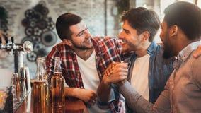 Amici maschii che si incontrano nel pub, birra bevente fotografia stock libera da diritti