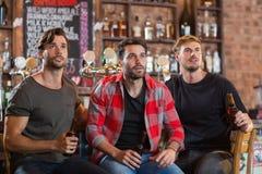 Amici maschii colpiti che distolgono lo sguardo mentre tenendo le bottiglie di birra Fotografie Stock
