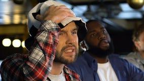 Amici maschii con il cappello e il vuvuzela di calcio deludenti circa la decisione dell'arbitro video d archivio