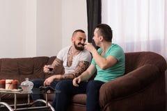 Amici maschii sorridenti che giocano i video giochi a casa Fotografia Stock Libera da Diritti