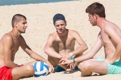 Amici maschii sorridenti del gruppo che si siedono sulla spiaggia Immagine Stock