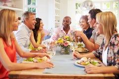 Amici maturi che si siedono intorno alla Tabella al partito di cena fotografie stock libere da diritti