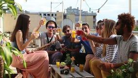 Amici multi-etnici allegri che ridono e che tostano con i cocktail al tetto video d archivio