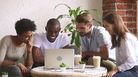 Amici multiculturali felici che esaminano computer portatile divertendosi commedia di sorveglianza archivi video