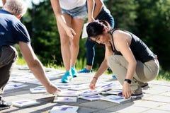 Amici multietnici che giocano cruciverba sul patio Fotografie Stock