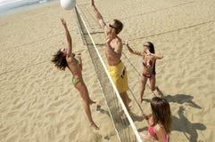 Amici multietnici che giocano pallavolo sulla spiaggia Fotografie Stock Libere da Diritti