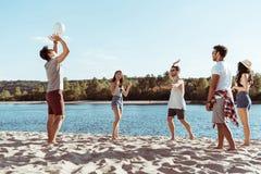 Amici multietnici che giocano pallavolo sulla spiaggia sabbiosa al giorno Fotografie Stock