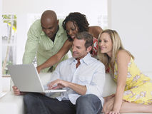 Amici multietnici con il computer portatile Fotografie Stock