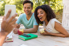 Amici multietnici sorpresi che esaminano l'esposizione del telefono cellulare Fotografie Stock Libere da Diritti