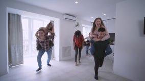 Amici multinazionali che hanno corse di a due vie faccia a faccia in appartamento che gode del partito di feste a casa in lento