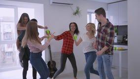 Amici multinazionali felici divertendosi e ballando con le tazze di plastica in loro mani nel partito dell'appartamento privato a