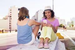 Amici multirazziali delle donne che si siedono e che utilizzano i telefoni cellulari nello stree immagini stock