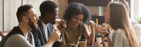 Amici multirazziali di immagine orizzontale che bevono caffè che mangia pizza al caffè immagine stock libera da diritti