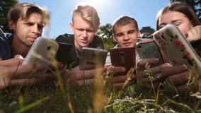Amici nel cerchio facendo uso degli smartphones sul prato inglese del parco stock footage