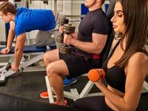 Amici nell'allenamento della palestra con l'attrezzatura di forma fisica Donne di addestramento Fotografia Stock