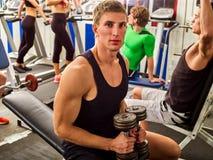 Amici nell'allenamento della palestra con l'attrezzatura di forma fisica Uomini di addestramento Immagini Stock