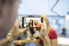 Amici nella barra che prende le foto con gli smartphones Immagine Stock Libera da Diritti