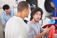 Amici nella lavanderia automatica immagini stock libere da diritti