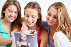 Amici o ragazze teenager che leggono rivista a casa Fotografia Stock Libera da Diritti