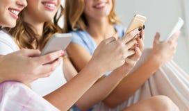 Amici o ragazze teenager con gli smartphones a casa Fotografia Stock